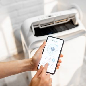 Woman holding smart phone with launched application for air condition control with ventilation unit on the background. Smart home concept